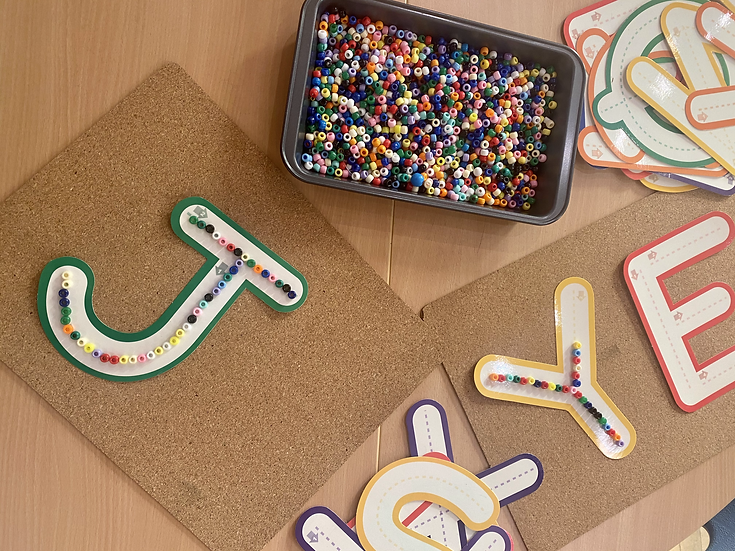 Plastic beads on paper letters