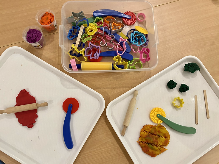 Play dough, tools, and a tray on a table