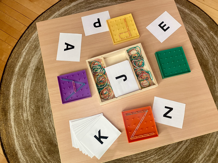 Letter cards and geoboards on a table in a classroom