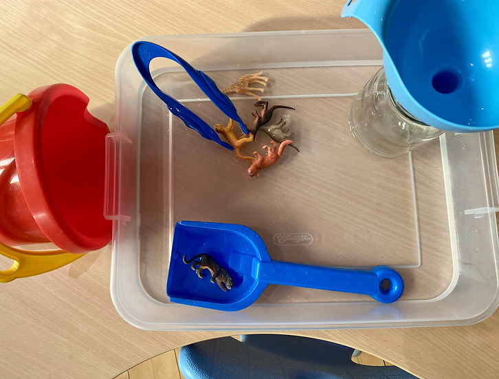 A plastic bucket with a collection of small toys in water.