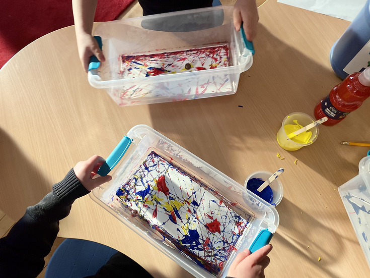Paper, paint, and marbles inside a small bucket.
