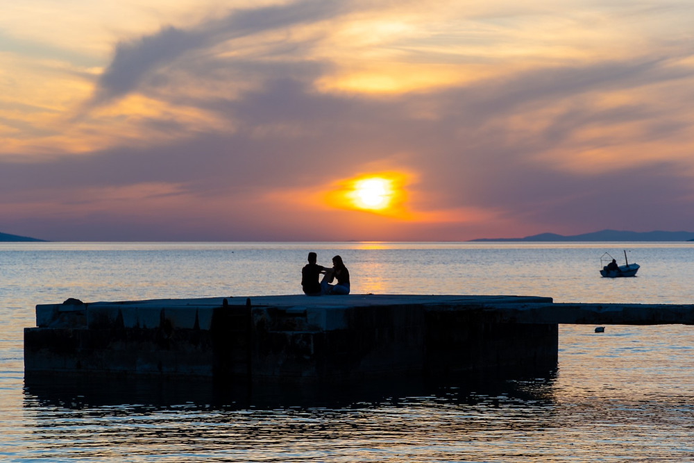 Romantic couple social distancing on a pier by the sea in Makarska Riviera sunset