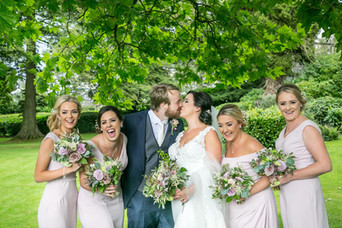 Wedding photograph of bride and groom having a laugh with the bridesmaids