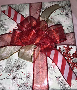 silver christmas wrapping paper, candy striped ribbon, red snowflake christmas ornament