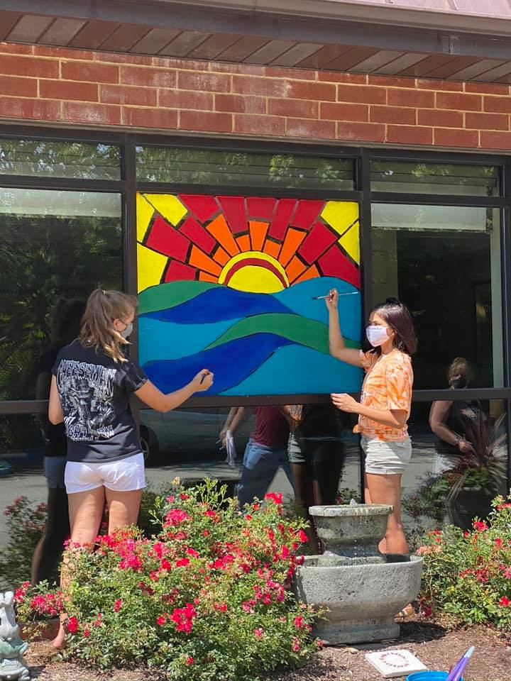 Anna & Joelle work on a sunrise mural