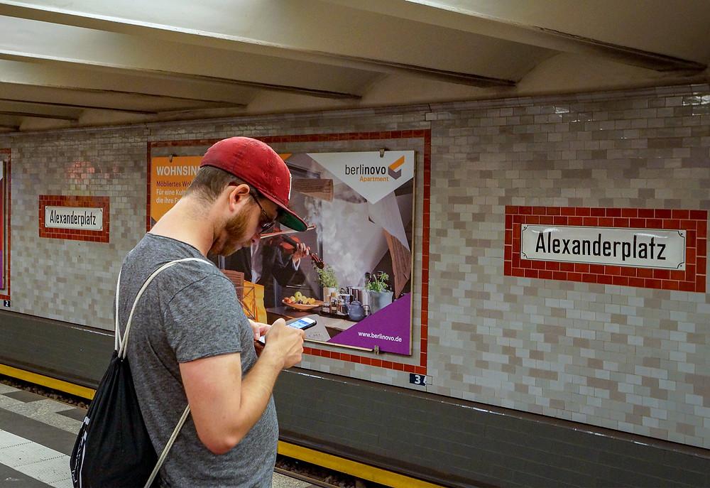 En berliner tjekker smartphonen på Ubahn-stationen Alexanderplatz