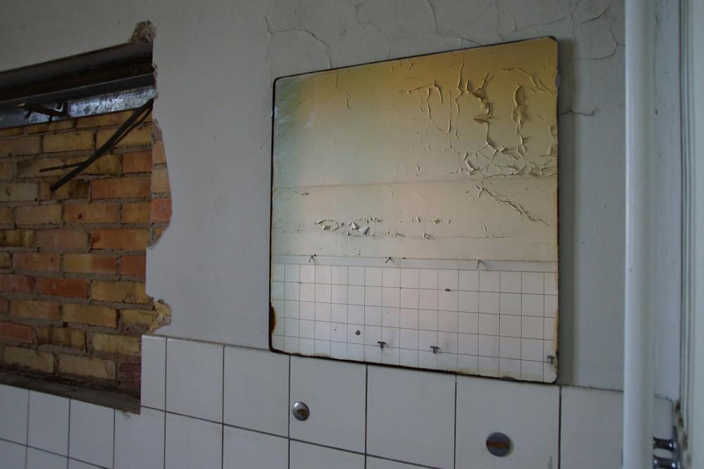 Et spejl har på mirakuløs vis overlevet tidens tand og bøllers hærgen på det nedlagte sygehus i Bogense.