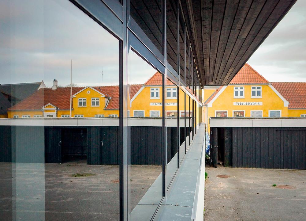 Gammelt møder nyt. En af de gamle købmandsgårde spejler sig i Nibe Kommunes Rådhus fra 1970.