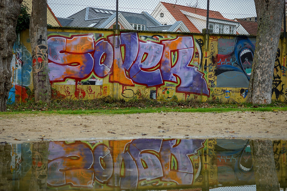 Muren rundt om Karolinelund er et langt lærred. Her spejler noget grafitti sig i en vandpyt.