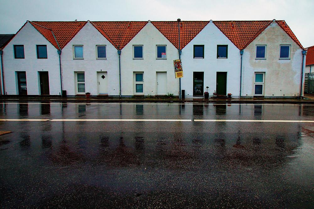 Rækkehusene på Strandgade ser lidt forsømte ud på en regnvejrsdag. Plakaten fra et omrejsende cirkus sætter prikken over i'et.