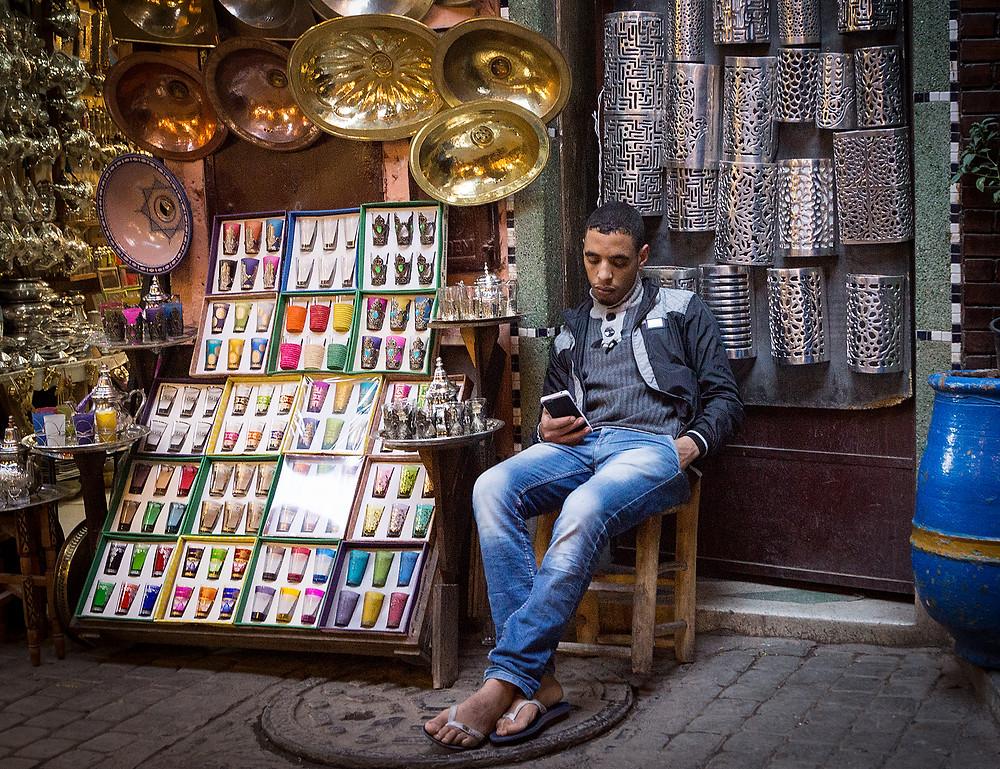 En ung købmand har glemt kunderne og tager en slapper med sin smartphone.