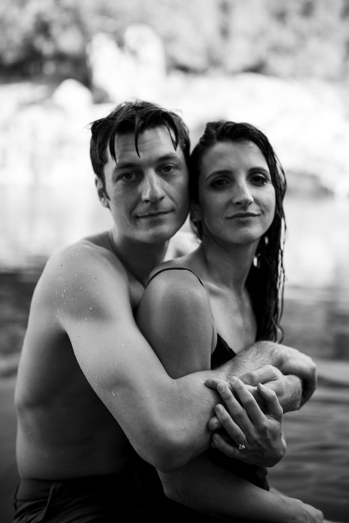 Couple hugging during their engagement session while swimming in Inks Lake in Texas
