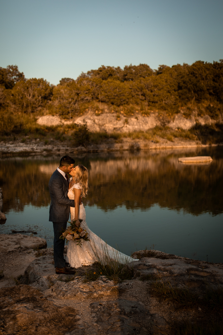 Bride and groom kissing on their elopement day next to a Texas river