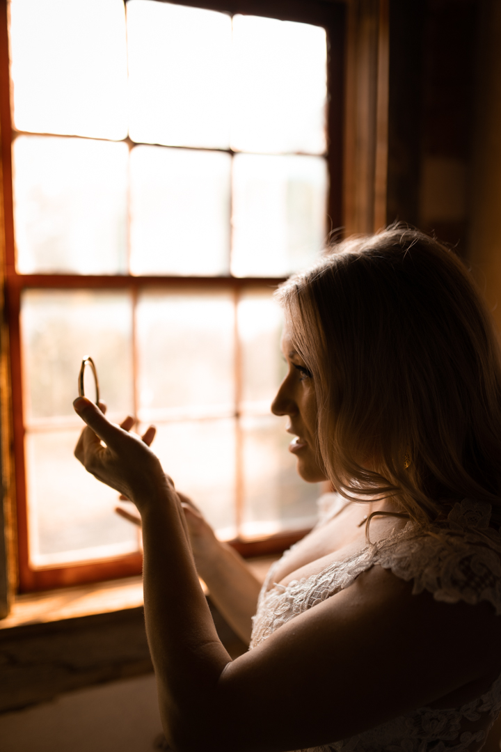 Bride looking in mirror while getting ready on her elopement day