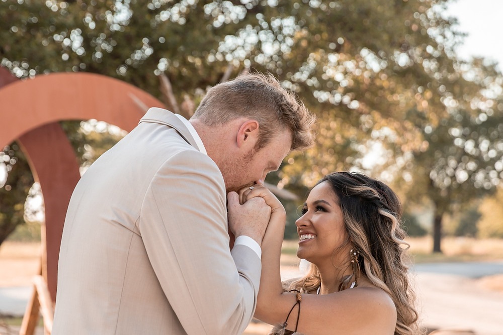 Groom kissing brides hands during their texas wedding ceremony at sparrow creek reanch