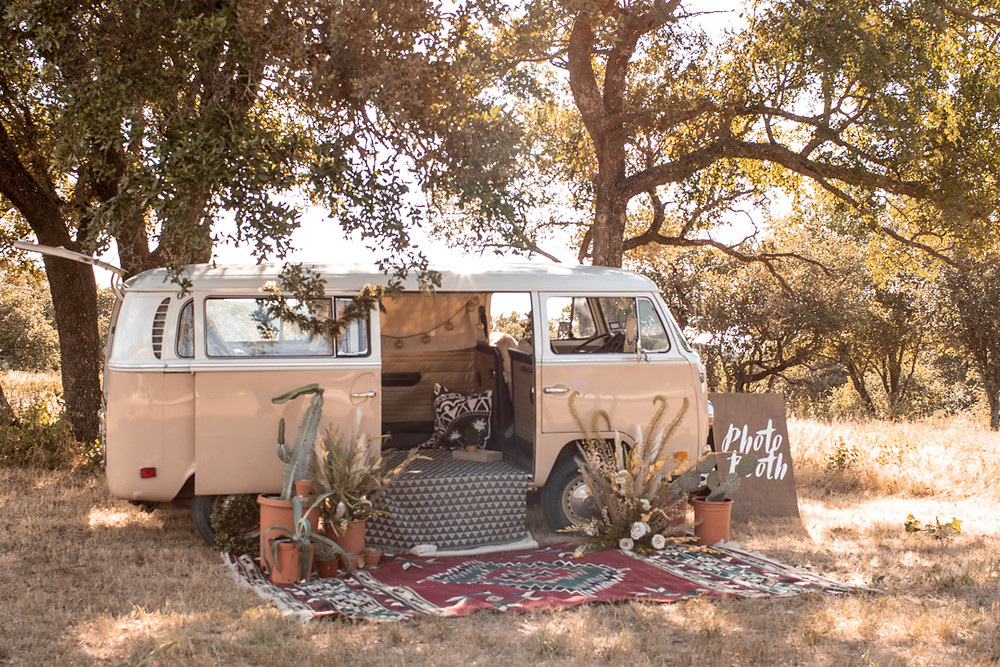 An earthy and yellow volkswagon photobooth set up with boho style florals and cactus in terra cotta pots.