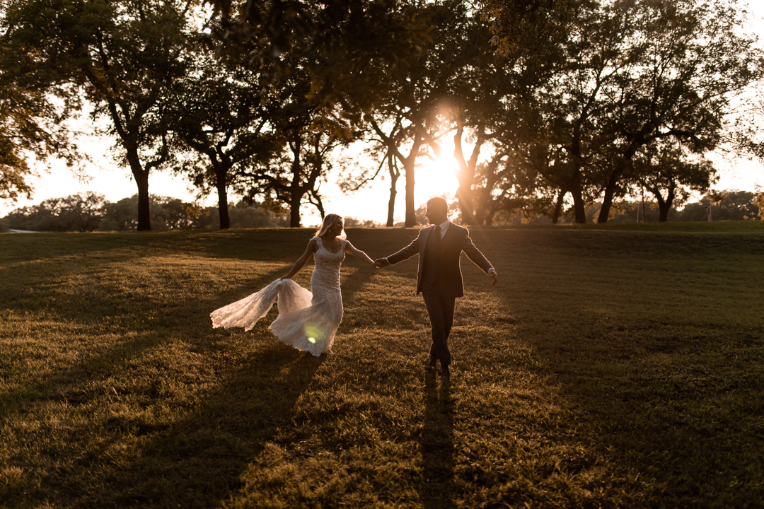 Bride and groom skipping through a field at sunset on their elopement day