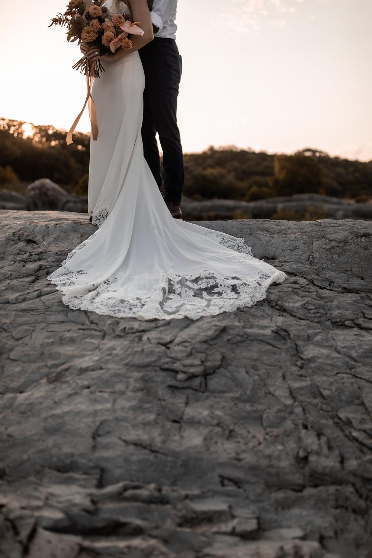 A brides wedding dress resting on the pedernales river limestone