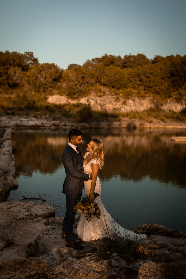 A bride and groom standing by a river during their adventure wedding in the texas hill country