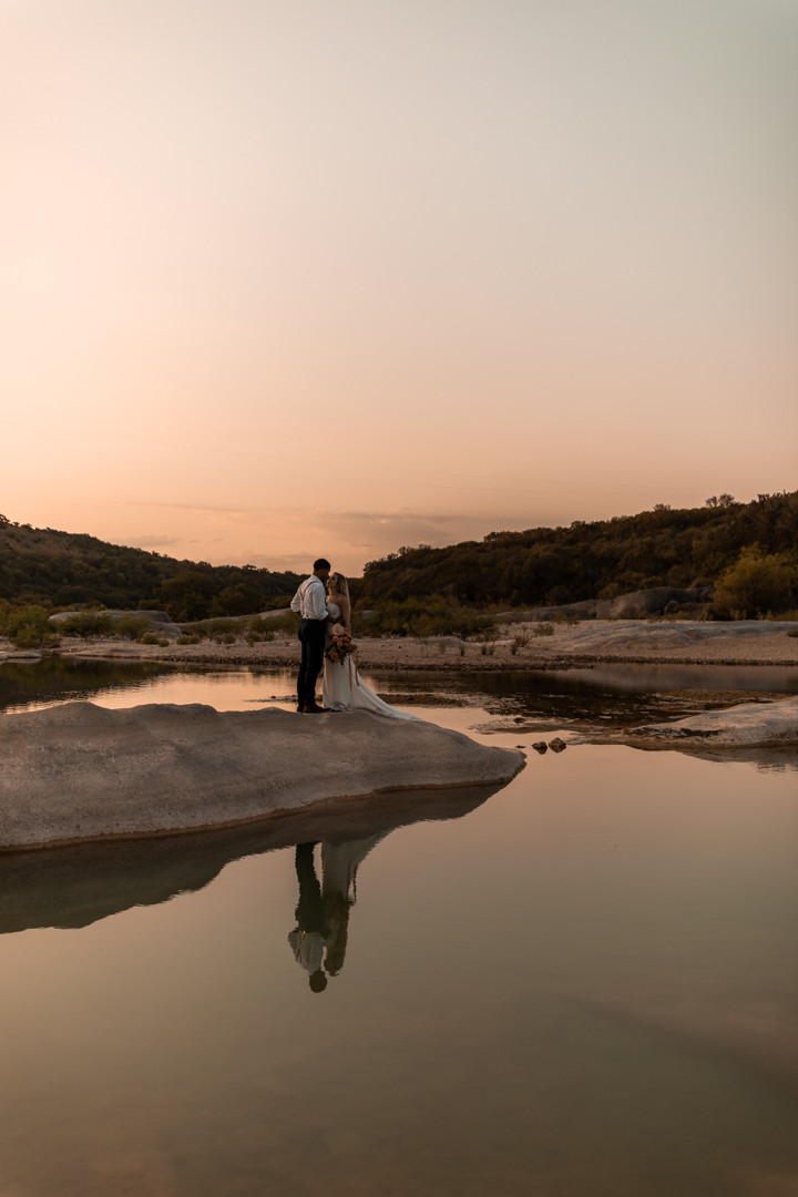 Bride and groom standing over the pedernales river during their texas elopement