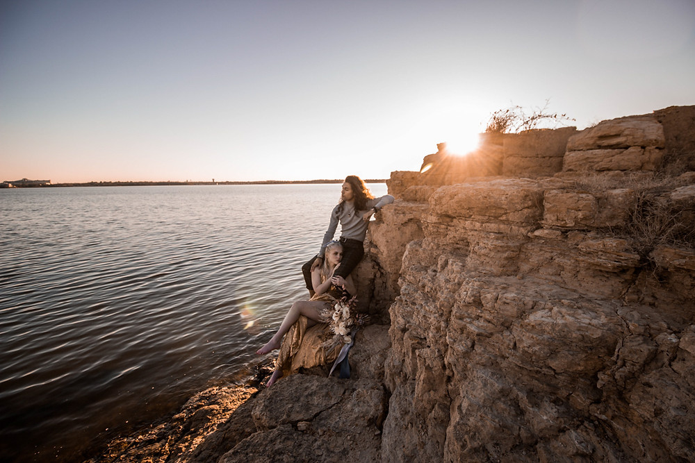 bride and groom sitting on a cliff during their texas adventure elopement