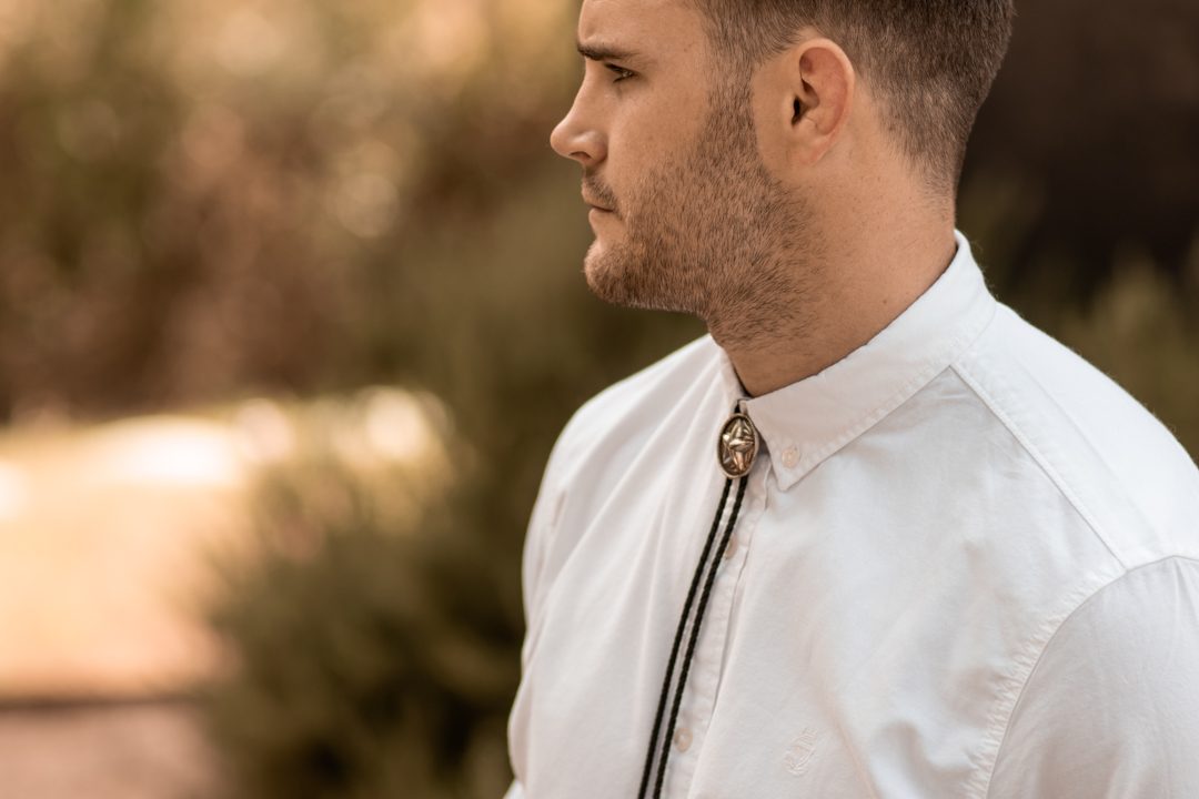 groom wearing a bolo tie at his modern fall texas wedding