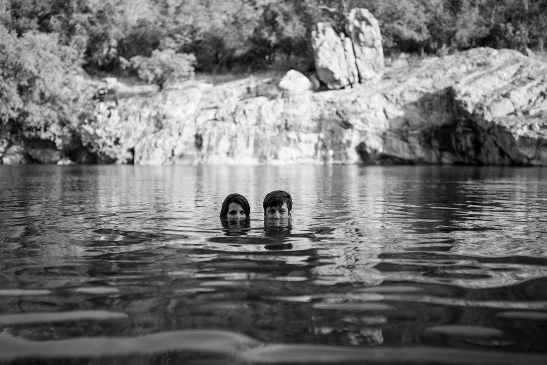 Couple swimming in Inks Lake during their adventurous engagement session
