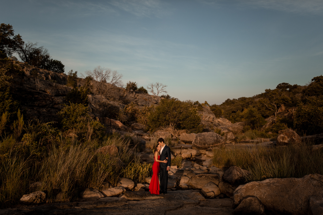 Couple hugging in the middle of a desert landscape during their adventurous engagement session in Texas