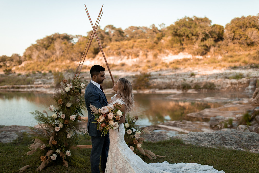 Bride and groom standing in front of their ceremony arch on their elopement day