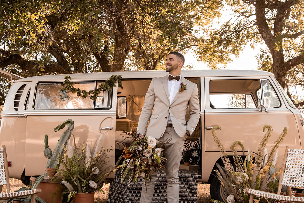 Groom standing in front of yellow volkswagen bus holding the brides boho bouquet