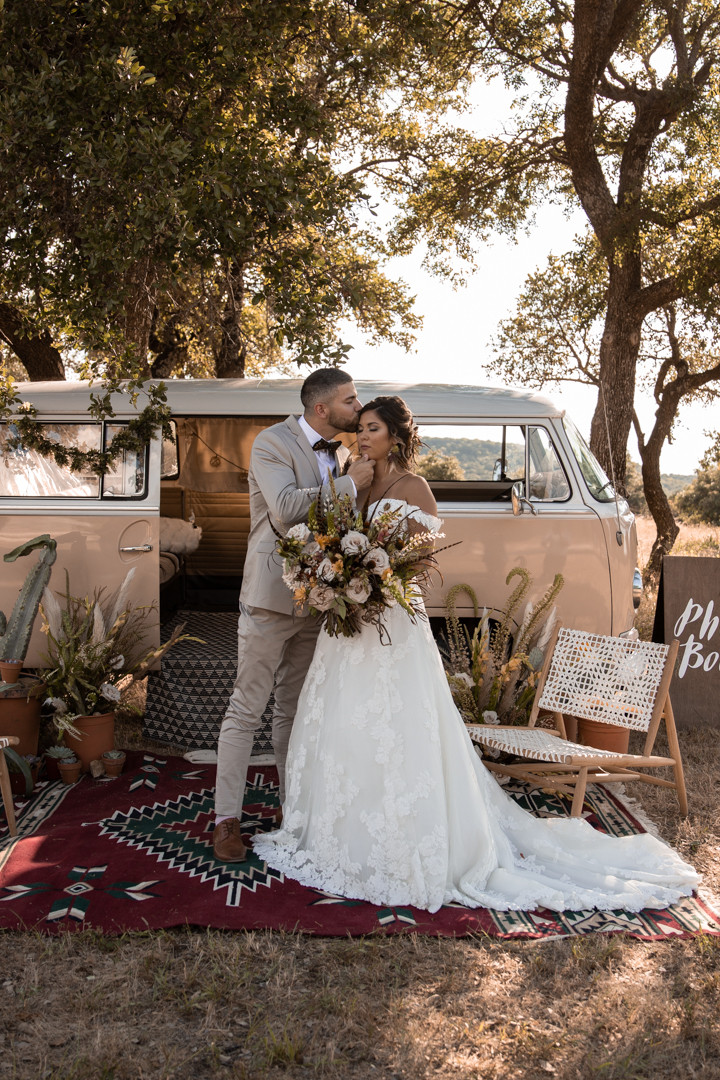Bride and groom kiss by a yellow volkswagen bus during their southwestern styled wedding in graham texas.