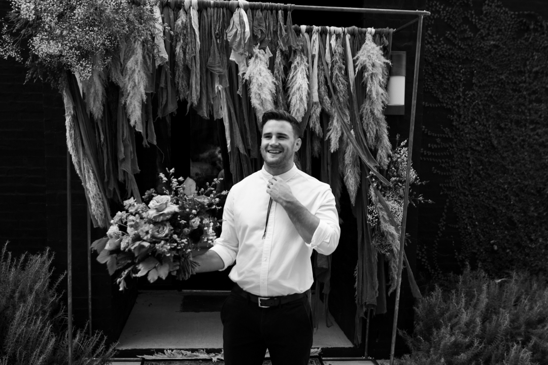 Groom holding his brides bouquet at a fall texas wedding