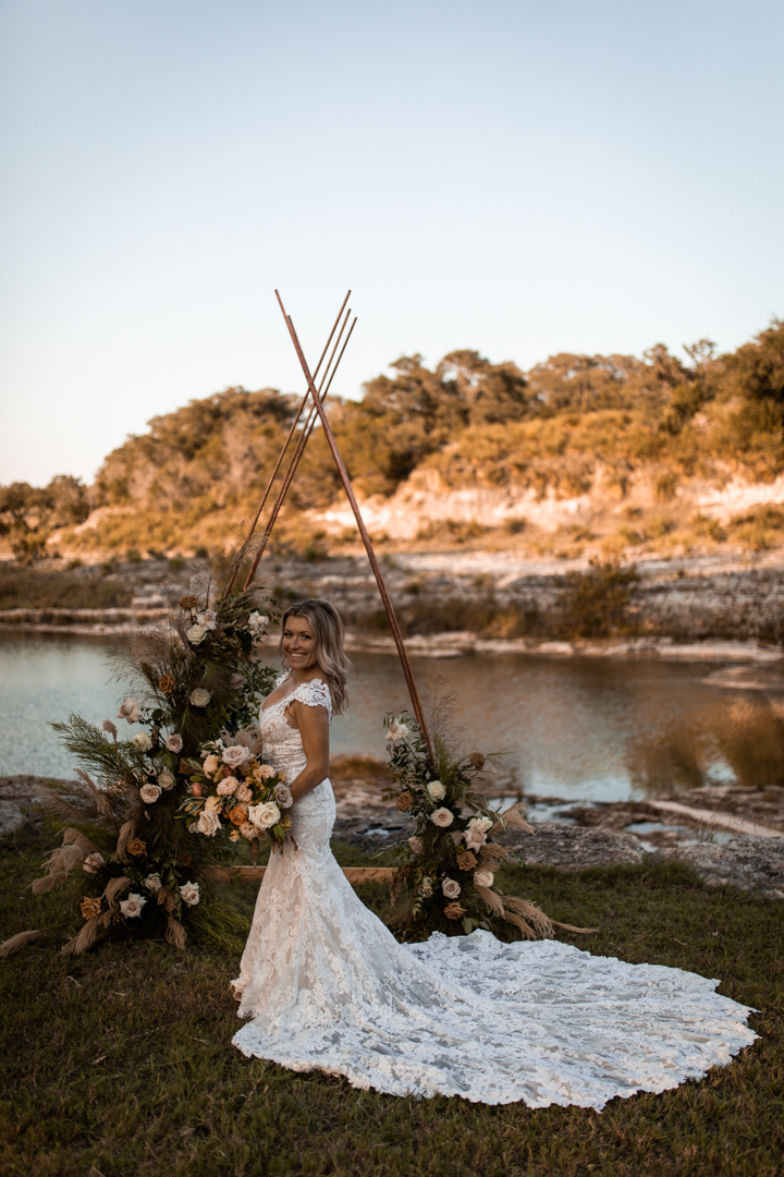 Bride standing at ceremony arch and holding her bouquet next to a texas river