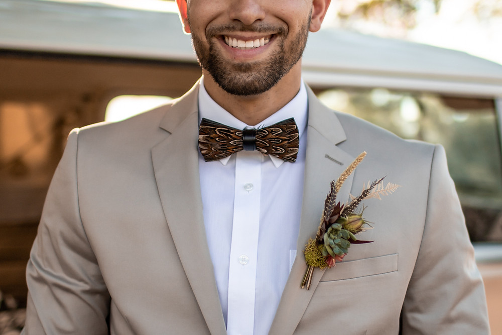 Groom in his suit in front of yellow volkswagen bus wearing a succulent boutonniere and feather bow tie