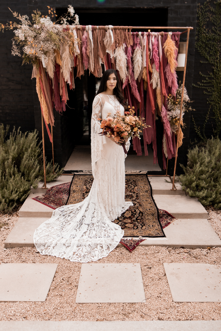 Bride wearing a Rue De Seine wedding dress and holding a bouquet at her fall wedding in Texas