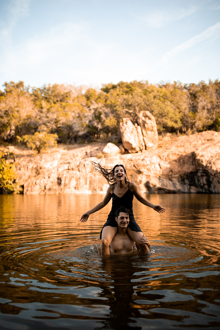 Couple swimming during their adventurous engagement session at Inks Lake