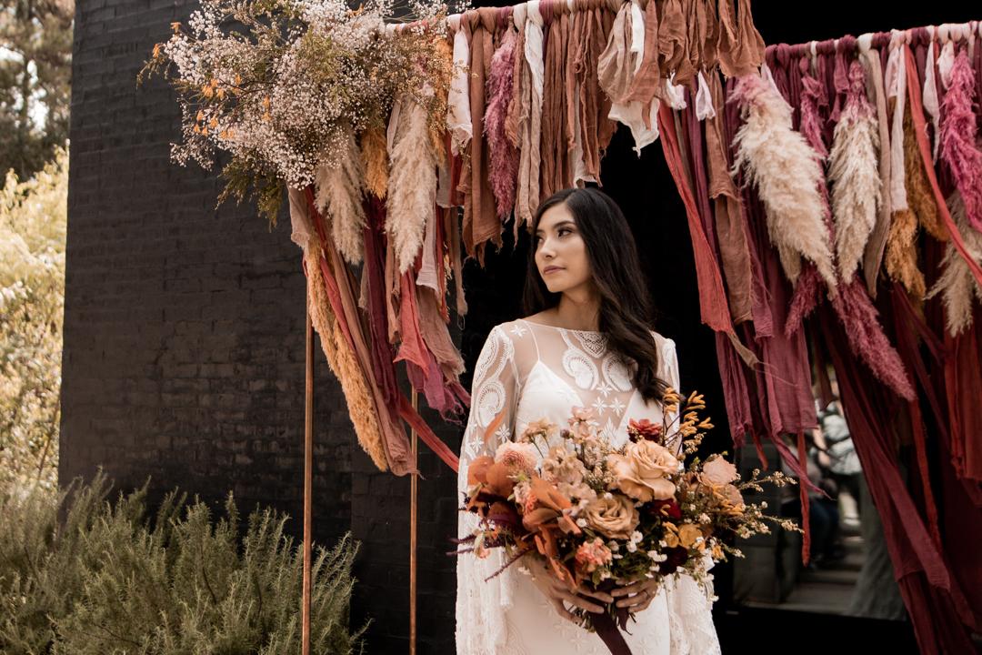 Bride in her wedding dress standing in front of her modern wedding arch in Texas