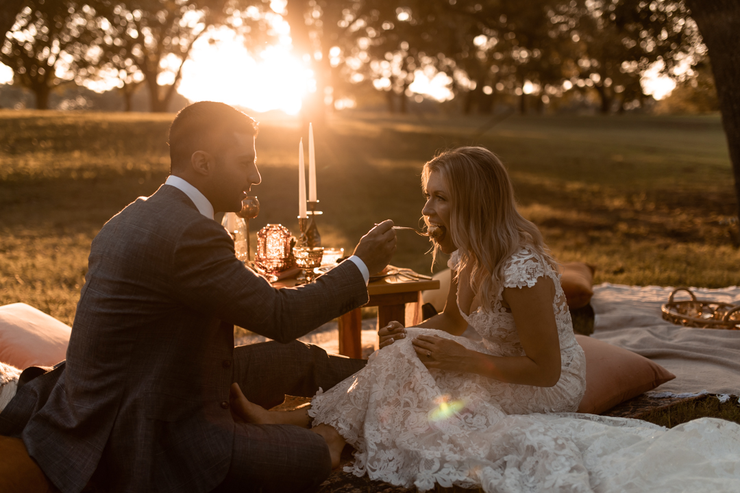 Bride and groom eating at their intimate picnic on their elopement day