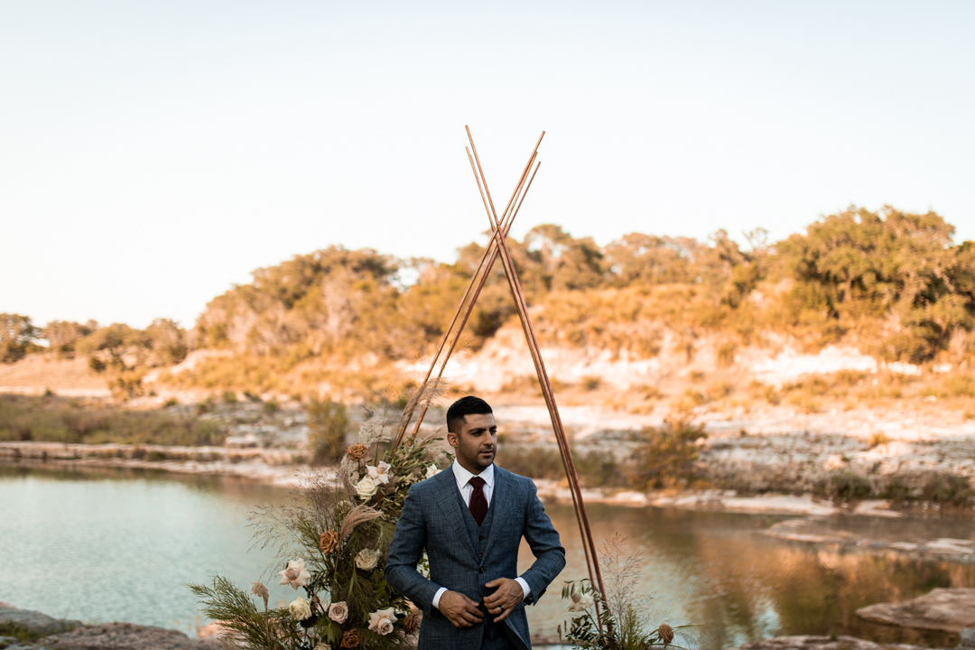 Groom standing at the ceremony arch on his elopement day