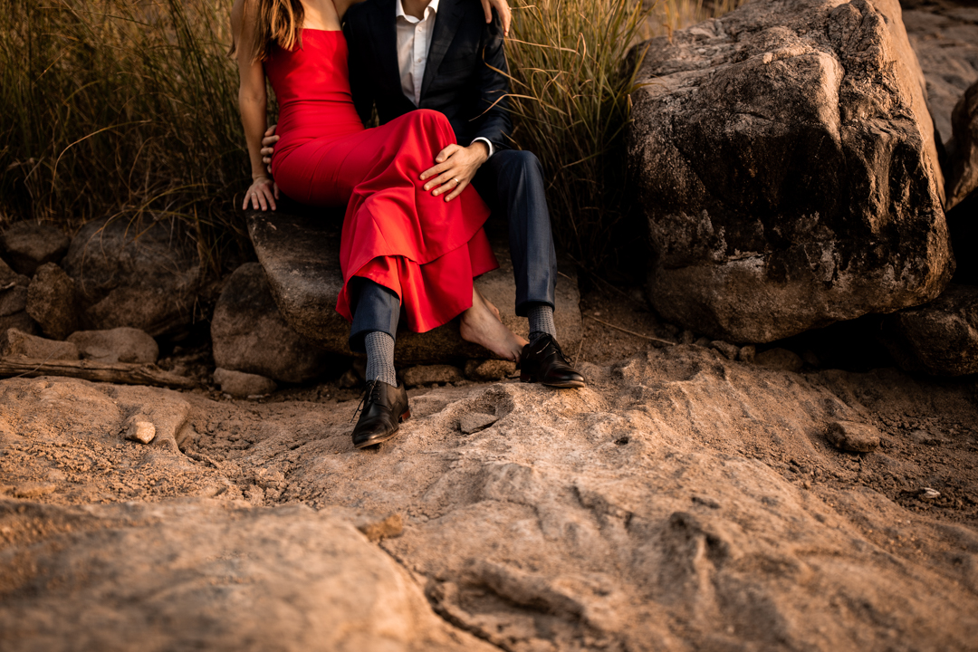 couple sitting together in a desert setting at inks lake in texas during their engagement session