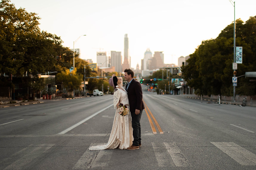 boho elopement on south congress bride and groom kissing with Austin skyline behind them