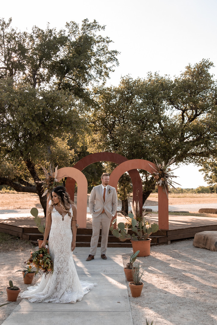 bride and groom standing in front of terra cotta and rust colored arches in the texas hill country