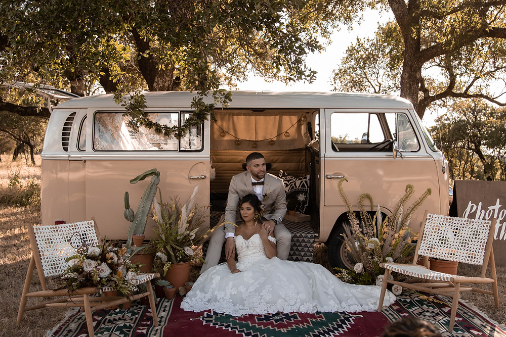 Bride and groom sit by a yellow volkswagen bus during their southwestern styled wedding in graham texas.
