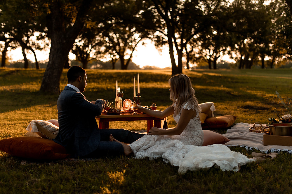 A couple sits down for a romantic picnic at their elopement