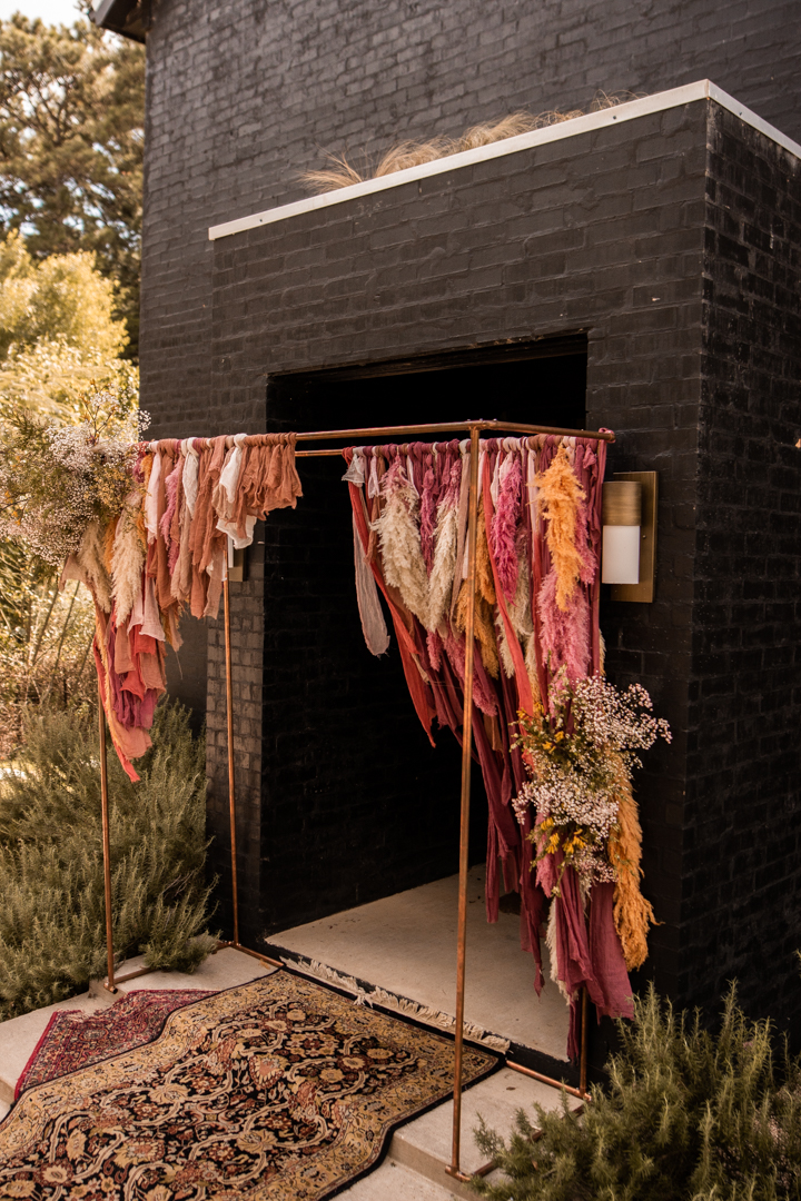 Modern wedding arch with shades of peach and pampas grass for a moody fall wedding in Texas