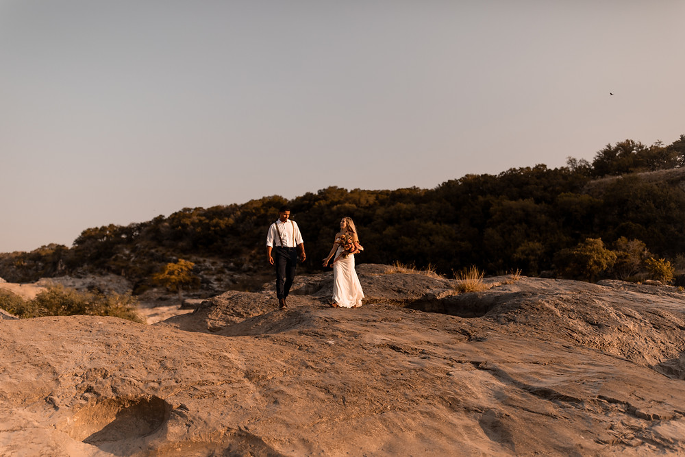 Couple hiking around during their adventure wedding at pedernales falls state park