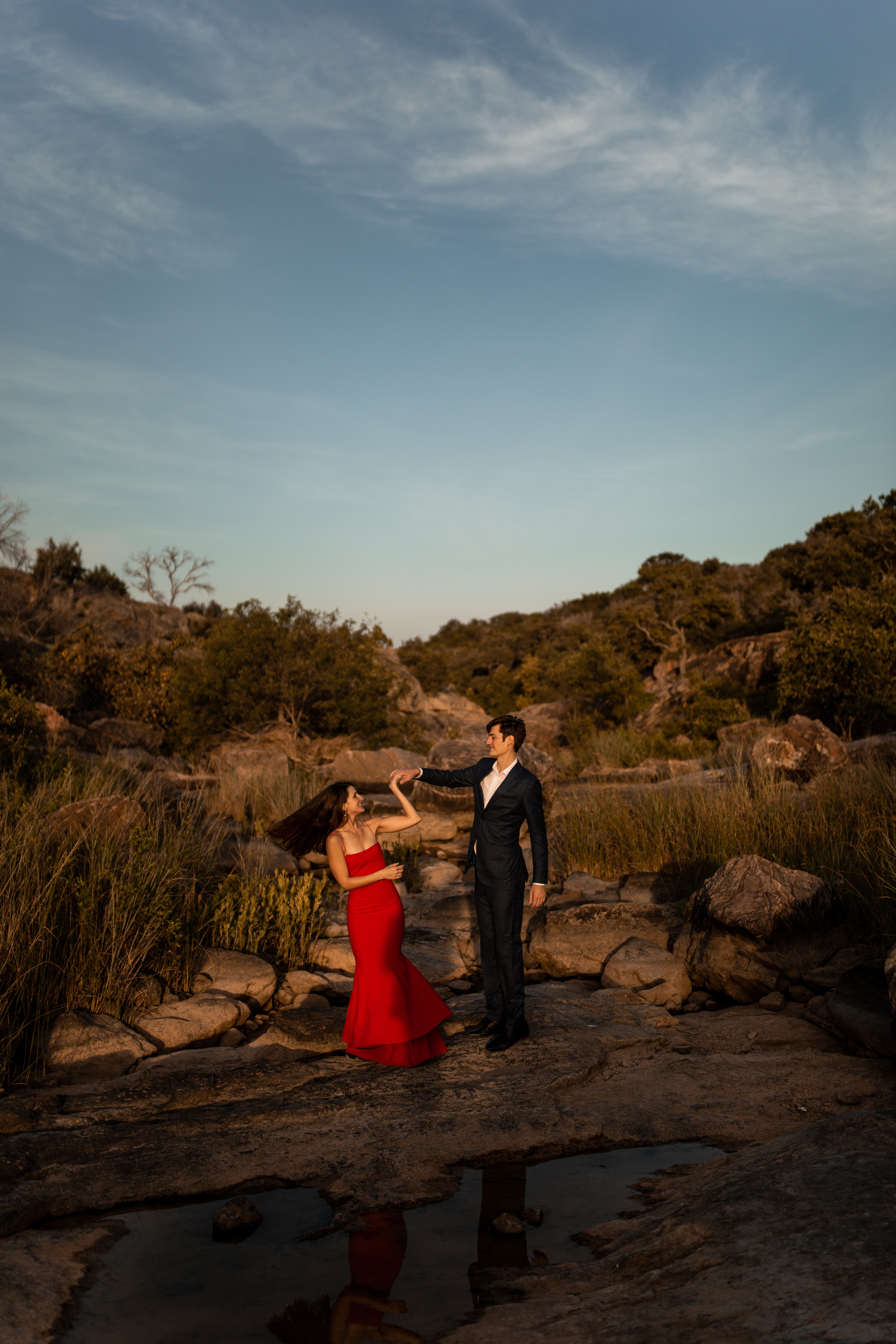 Couple dancing in the desert during their adventurous engagement session at Inks Lake State Park in Texas