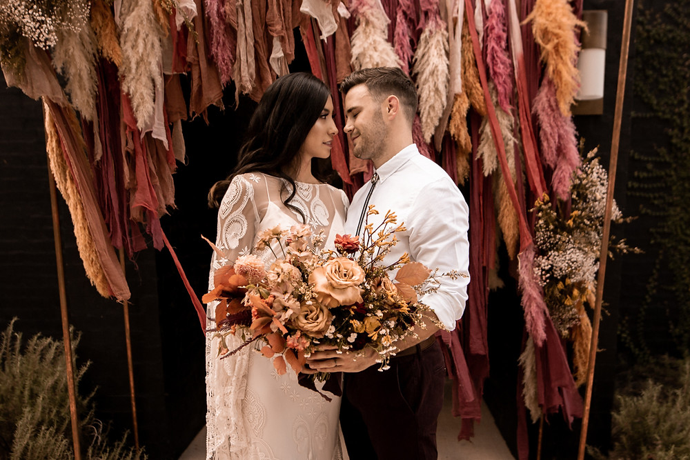 Bride and groom holding a bouquet during their moody fall wedding