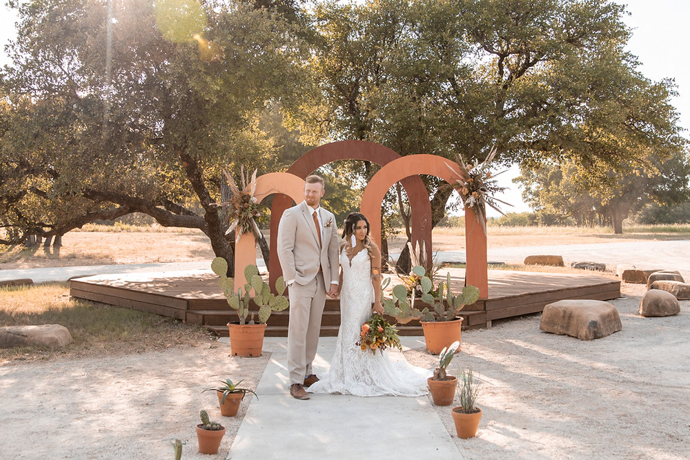 Bride and groom get marriend in front of terra cotta arches in the texas hill country