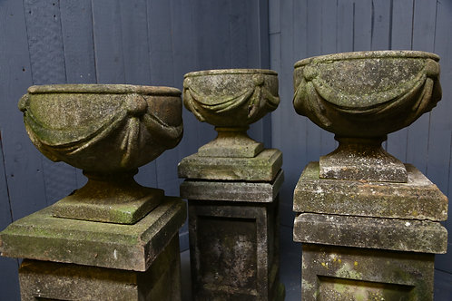 C20th Trio of composition urns with swags